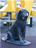 Metal sculpture of a seated dog titled