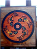 Wooden painted wall art of fish in a Native American spirit wheel titled