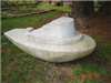Medium-size stone sculpture of a tugboat titled