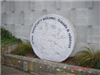 Small round granite sculpture with inscriptions titled